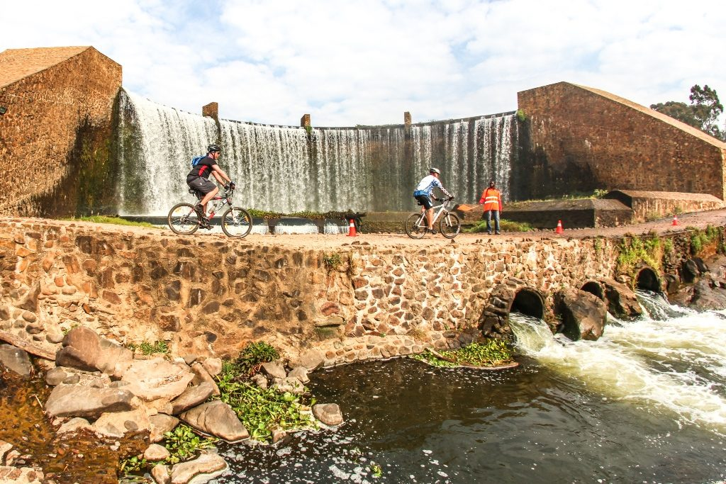 Riders pass below the waterfall cascading over the weir of Lake Heritage during Stage 2 of the Glacier Cradle Traverse, on Saturday the 6th of May 2017. Photo by Oakpics.com.